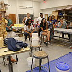 Class members in the three-week summer course look on as visiting artist Steve Prince talks about the nearly-completed mural they made to commemorate the 50th anniversary of William & Mary's first African-American residential students.
